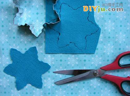 在DIY的布藝上畫好的圣誕樹模型,用剪刀剪下圖案